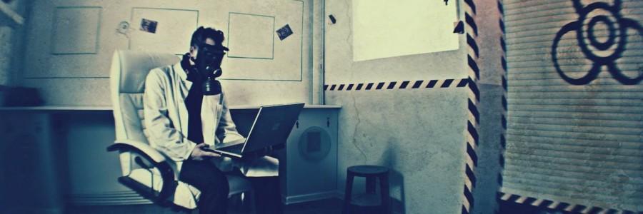 Ein Mann mit Laborkittel und Atemmaske sitzt mit einem Laptop in einem Labor.