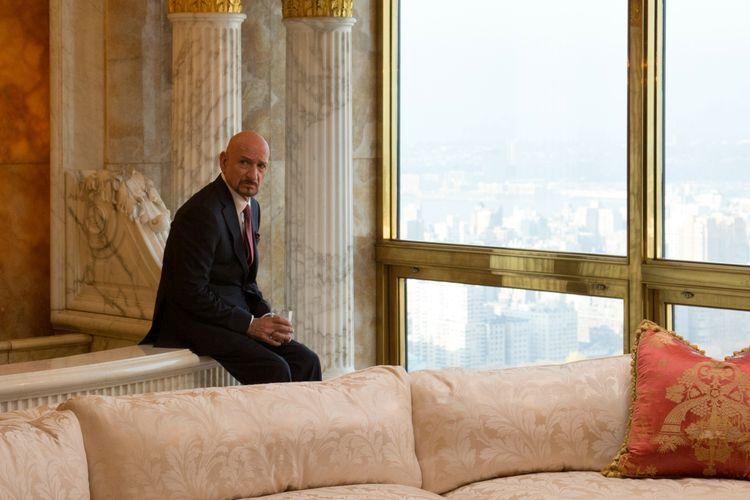 Ein älterer Mann im Anzug sitzt in einer protzigen Suite. Er sieht nicht glücklich aus.