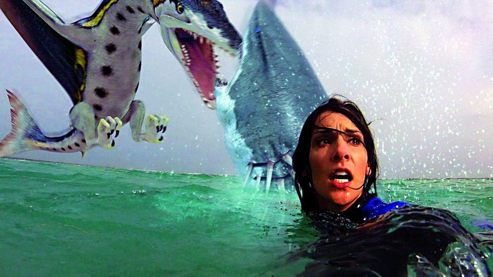 Eine Taucherin im Wasser, hinter ihr kämpfen Pteracuda und Sharktopus gegeneinander.