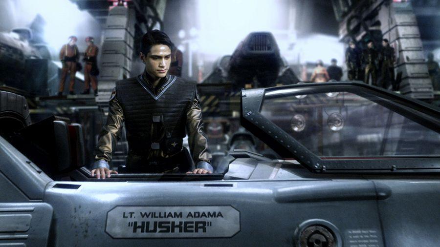 Szene aus Blood and Chrome: Ein junger Mann steht in einem futuristischen Hangar und schaut ins Cockpit eines Kampffliegers.