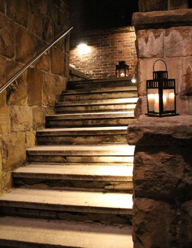 Eine Treppe in einem alten Herrenhaus, beleuchtet von Kerzenlaternen.