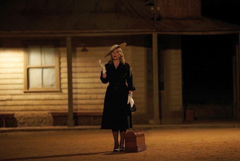 Szene aus The Dressmaker: Eine Frau im schwarzen Kleid mit Hut und weißen Handschuhen steht nachts mit einer Reisetasche vor einem Farmhaus.