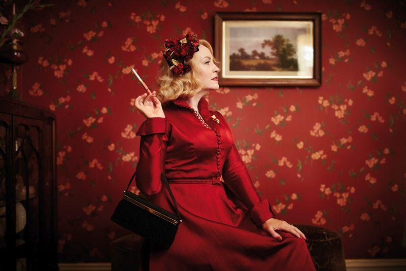 Eine Frau im roten Kleid vor einer roten Tapete.