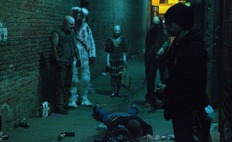 Ein Seitengasse, ein böser Clown, jemand im blutbefleckten Hasenkostüm, ein Mädchen und ein Mann mit gruseligen Masken stehen über einer Leiche am Boden. Im Vordergrund ein Mann mit Pudelmütze und Brille.
