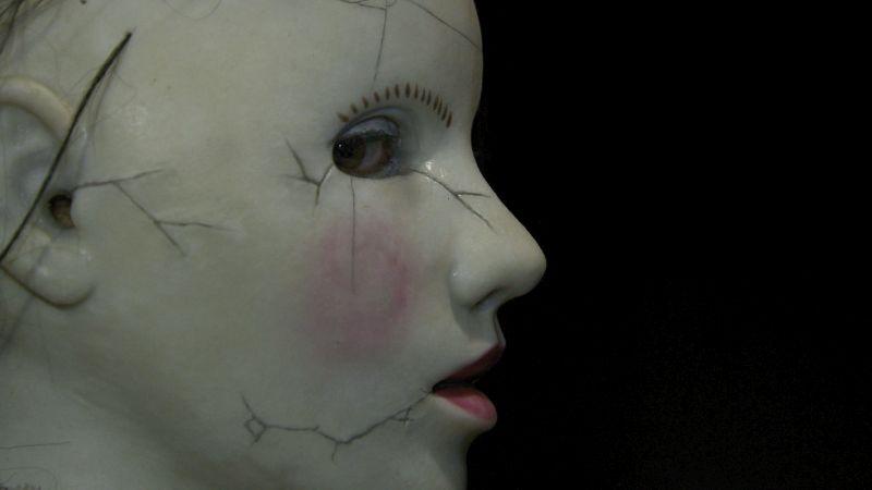 Seitenansicht einer Porzellanmaske mit Rissen, ein Auge ist hinter dem Augenloch zu erkennen.