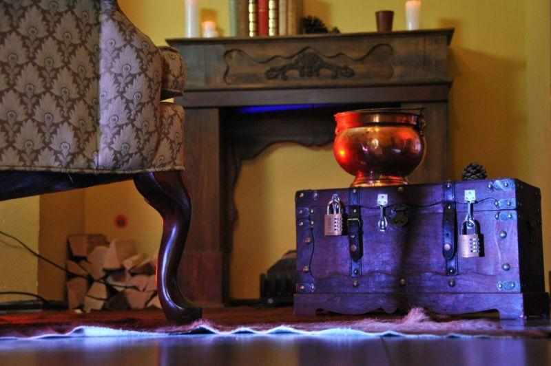 Requisiten aus dem Quexit-Escape Room Herr der Dinge: Ein Couchbein, eine verschlossene Truhe mit einem Kupferkessel darauf und ein Bücherboard im Hintergrund