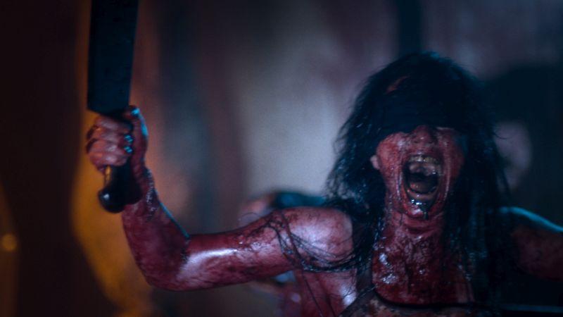 Szene aus Baskin, eine blutverschmierte schreiende  Frau mit Augenbinde und einem großen Messer in der erhobenen Hand.