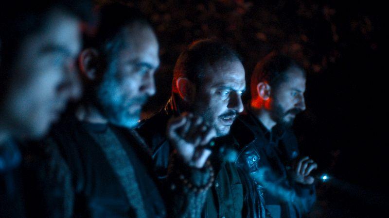 Vier Männer im Halbdunkel schauen fassungslos nach rechts.