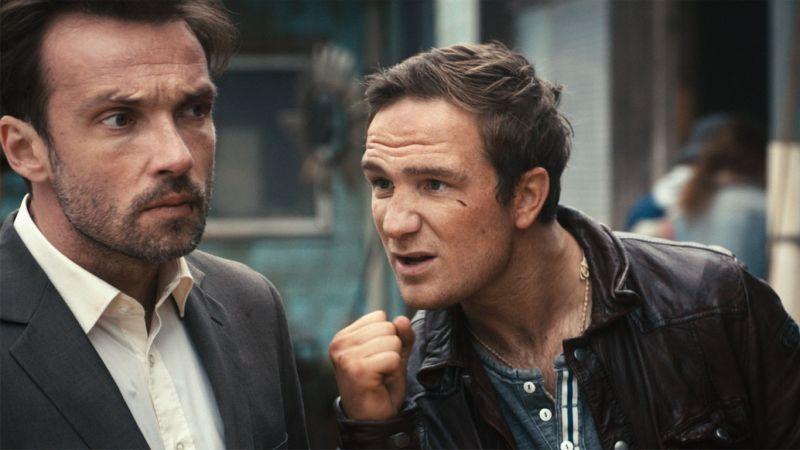 Zwei Männer in den Dreißigern, einer mit Anzug und Dreitagebart, der andere in Lederjacke.
