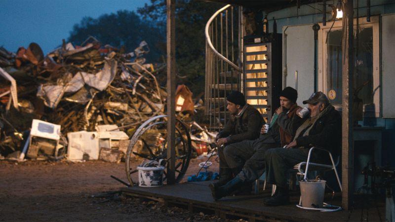 Drei Männer sitzen dick eingepackt auf der Veranda. Im Hintergrund ein riesiger Schrottberg.