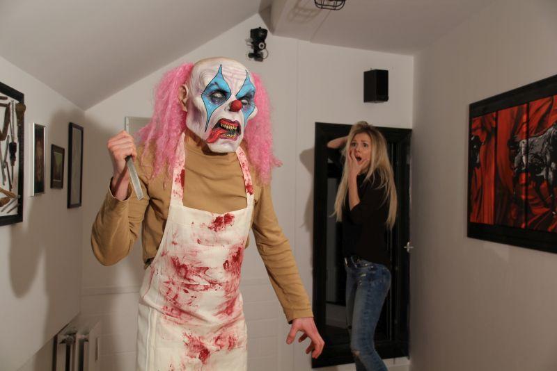 Ein Mörderclown mit blutiger Schürze und Messer in der erhobenen Hand sowie eine schreiende blonde Frau.