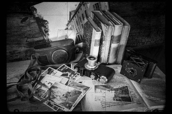 Foto vom Teamescape Düsseldorf, zu sehen sind alte Bücher, eine Kamera und das Foto eines alten Hauses.