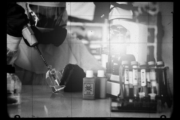 Foto vom Teamescape Düsseldorf, zu sehen ist ein Labor mit zahlreichen als gefährlich markierten Substanzen und eine Person in einem Schutzanzug.