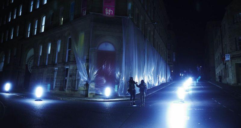 Eine Großstadtszene nachts, die Häuser sind mit Plastikfolie umhüllt, auf den Straßen stehen hell gleißende Lampen. Eine Frau und ein Mädchen stehen sich gegenüber, die Frau hat eine Atemmaske auf.