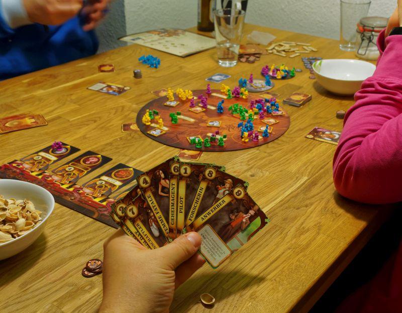 Eine Hand mit aufgefächerten Karten aus Aufbruch zum Roten Planeten, im Hintergrund das runde Mars-Spielbrett und die Spielfiguren.