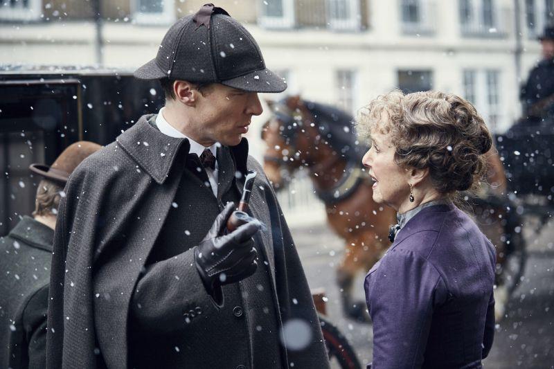 Szenenbild aus Sherlock Die Braut des Grauens: Ein Mann mit Deerstalker-Mütze und Pfeife sowie eine Frau in einem viktorianischem Kostüm vor einer Droschke im Schnee.