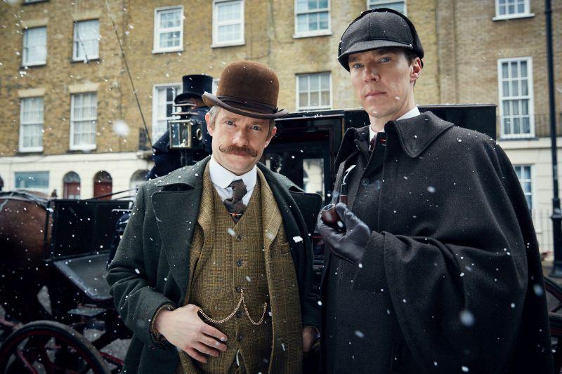 Szenenbild aus Sherlock Die Braut des Grauens: Ein Mann mit Schnäuzer und Melone, ein Mann mit Deerstalker-Mütze und Pfeife vor einer Droschke im Schnee.