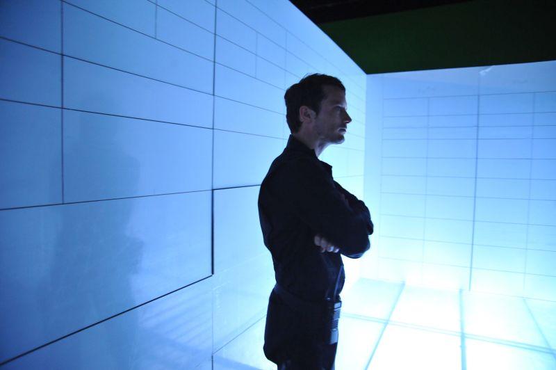 Ein schlanker Mann in dunkler Kleidung steht mit verschränkten Armen in einer blauen Kammer.