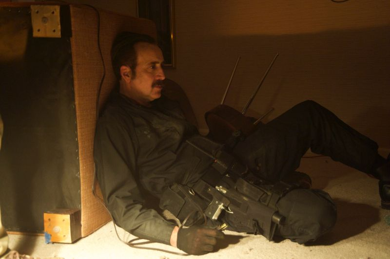 Ein älterer Mann mit Schnäuzer liegt in schwarzer Kampfmontur mit desolatem Gesichtsausdruck hinter einem umgekippten Möbelstück.