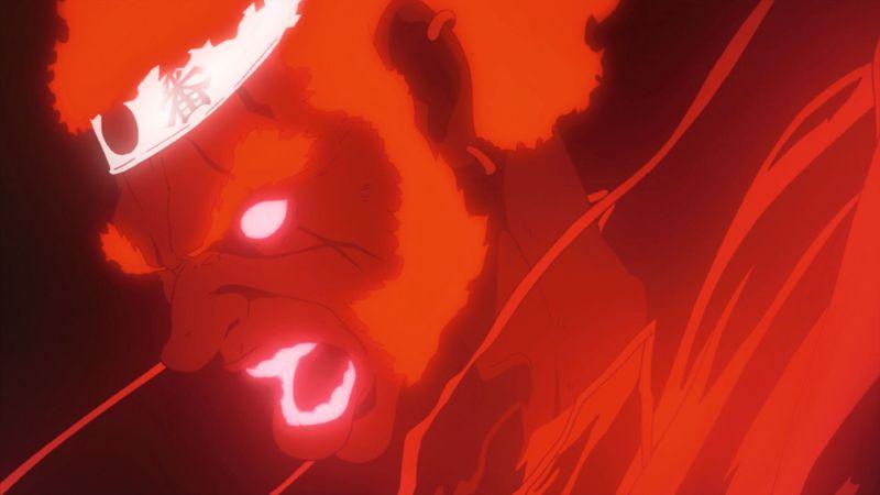 Ein rotglühender Mann mit mächtigen Kotletten und einem Stirnband.