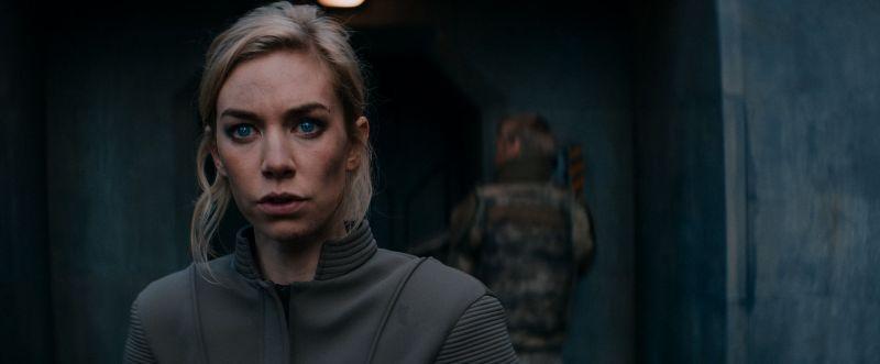 Szene aus Kill Command: EIne blionde Frau mit blauen Augen in einem Betonbunker, im Hintergrund ein Soldat in Tarnfleck._Szenenbilder_01.72dpi