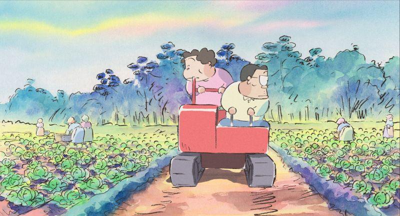 Herr und Frau Yamada fahren auf einem Raupenfahrzeug durch ein Kohlfeld.