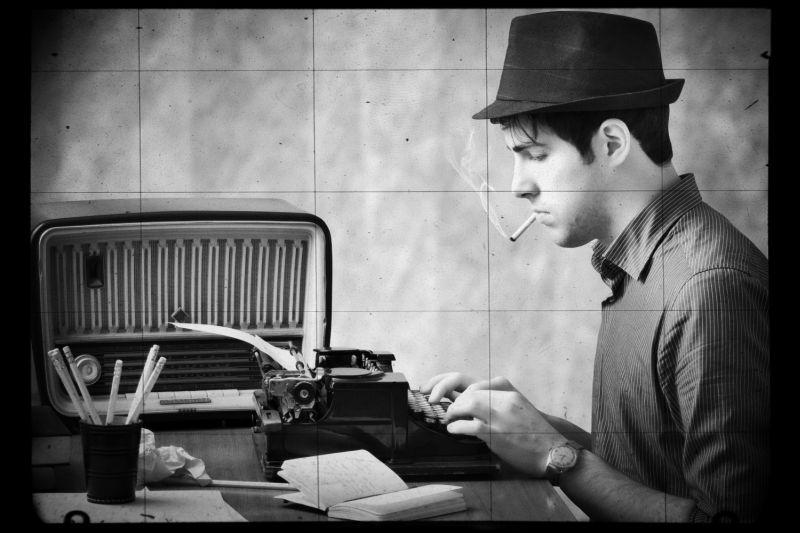 Ein rauchender Mann mit Hut sitzt an einer Schreibmaschine, dahinter ein altmodisches Radio.