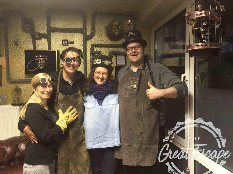Im The Great Escape: Zwei Frauen und zwei Männer mit Steampunk-Accessoires wie Zylindern und Goggles in einem Raum voller Rohre und Zahnräder.