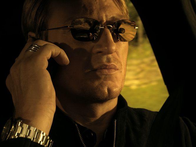 Ein blonder Mann mit verspiegelter Sonnenbrille, ein Handy am Ohr.