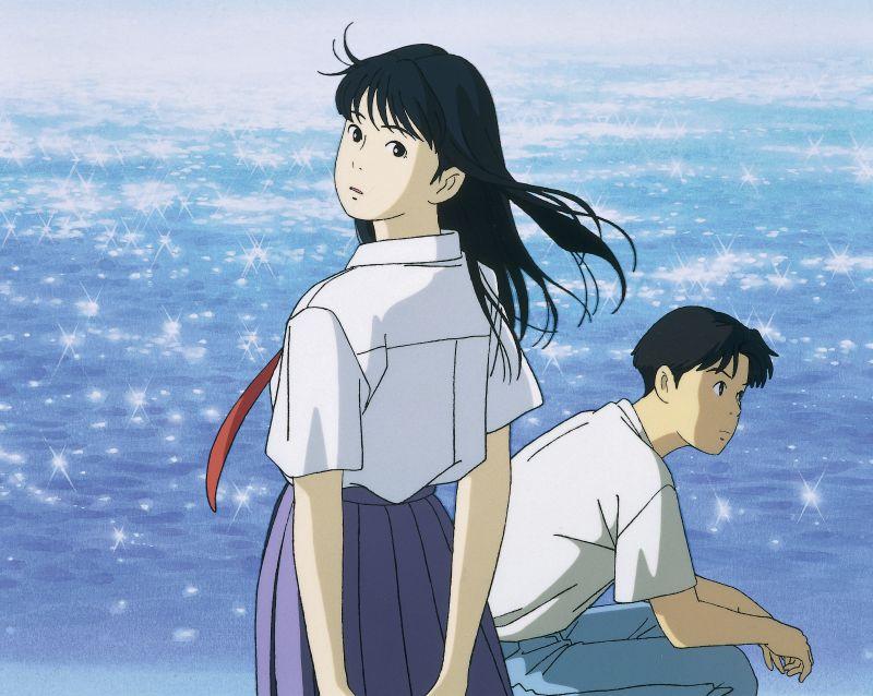 Szene aus Flüstern des Meeres (Ocean Waves): Zwei junge Menschen, ein Mann und eine Frau, vor der glitzernden Meeresoberfläche.