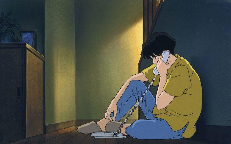 Szene aus Flüstern des Meeres (Ocean Waves): EIn junger Mann sitzt am Boden und telefoniert über ein schnurgebundenes Telefon.
