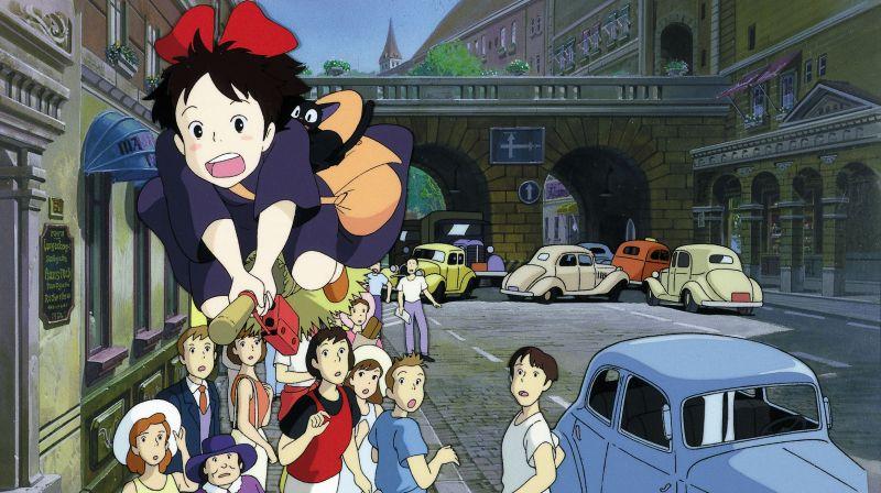 Ein Mädchen mit roter Schleife im Haar fliegt auf einem Besen über eine Menschenmenge, die ihr ungäubig hinterherstarrt.