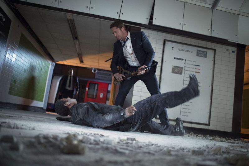 Ein Mann liegt in eine Londoner Metro-Station am Boden. über ihm ein Mann ihm Anzug mit einem Gewehr in den Händen.