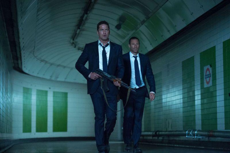 Zwei Männer in dunklen Anzügen gehen durch eine Metro-Station, einer ist mit einem Geweht bewaffnet.