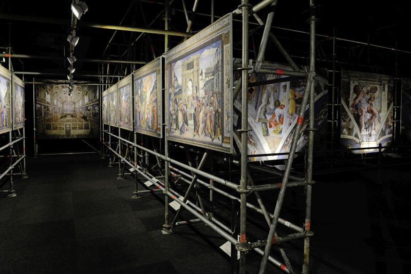 Ausstellung Der Andere Blick: Mehrere Gemälde, die an Baugerüsten angebracht sind.