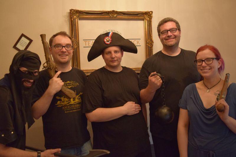 Foto vom Teamcrack Dortmund: 5 Personen, eine Frau und vier Männer, posieren mit napoleonischen Requisiten.