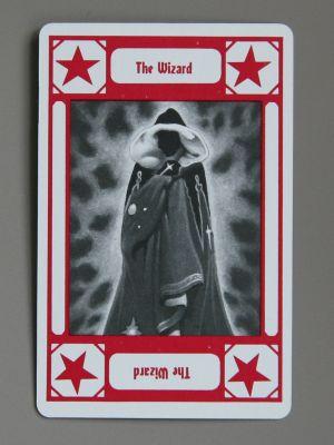Die Karte im Tarot-Stil zeigt eine Gestalt in Robe, deren Gesicht nicht zu erkennen ist. Darunter der Schriftzug The Wizard
