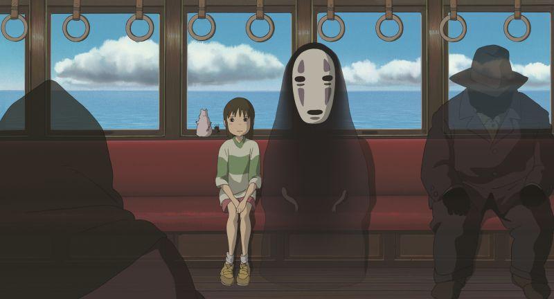 Szene aus Chihiros Reise ins Zauberland: Ein kleines Mädchen in einer Straßenbahn mit dunklen schemenhaften Gestalten. Eine davon trägt eine weiße Gesichtsmaske.