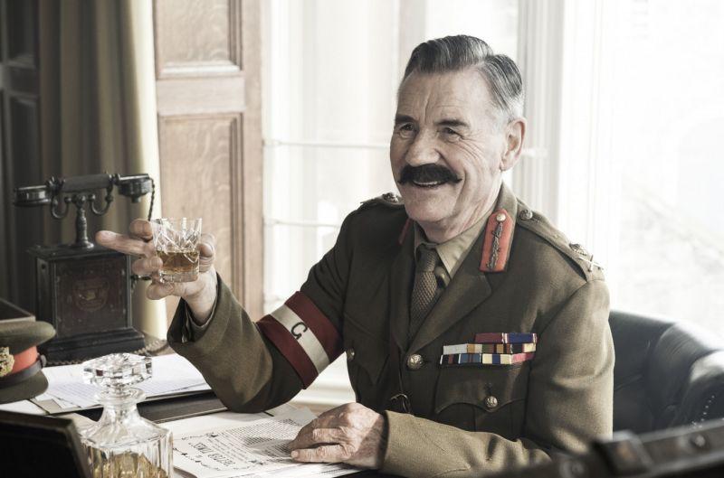 Ein älterer Mann mit Schnurrbart und pomadiertem Haar in einer Militäruniform sitzt an einem Tisch. Er hebt ein Whiskyglas.
