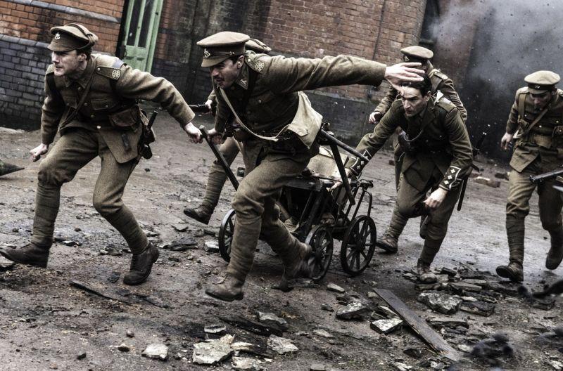 Mehrere englische Soldaten des ersten Weltkrieges laufen geduckt durch gegnerisches Feuer.
