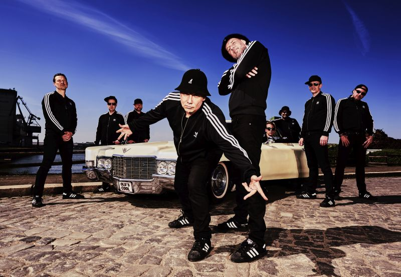 Neun Männer in schwarz-weißen Adidas-Anzügen posieren in Gangsterposen am Hafen.