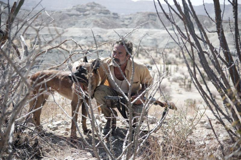 Jeffrey Dean Morgan in Desierto: Ein Mann mit Bart und Gewehr kniet in der Wüste neben einem Schäferhund.