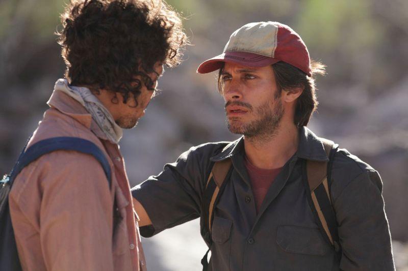 Ein Mann mit Kappe legt einem Mann mit Lockenkopf seine Hand auf die Schulter und schaut ihn dabei traurig an.