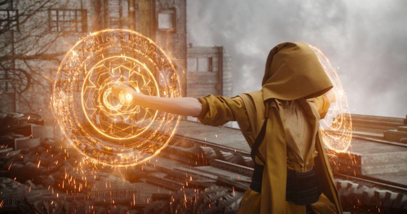 Eine Gestalt in einer gelben Kutte, deren Hände von feurigen Mandalas umgeben sind.