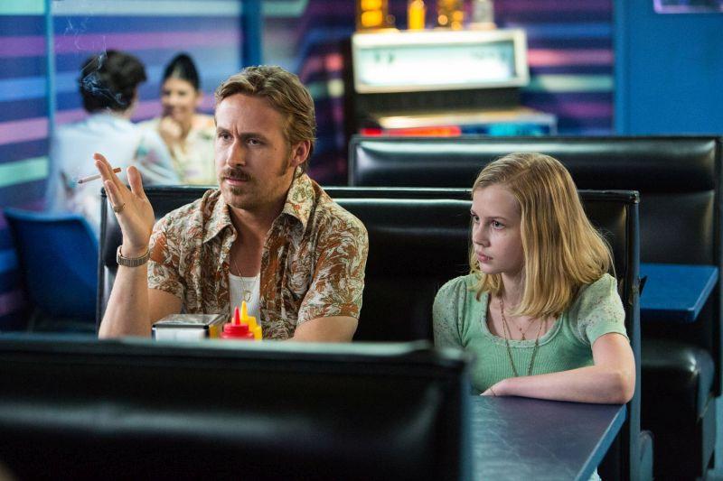Ein Mann in buntem Hemd mit einer Zigarette in der Hand sitzt in einem Diner. Neben ihm sitzt ein etwas zwölfjähriges Mädchen.