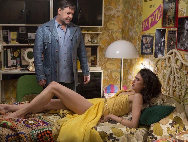 Ein Mann in einer blauen Lederjacke steht an einem Bett. Darauf liegt eine Frau in einem gelben Kleid.