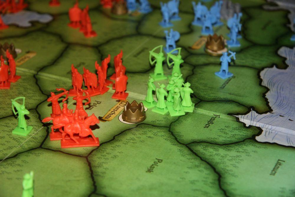 Das Spielbrett von Risiko Europa; Miniaturen von Reitern, Bogenschützen und mittelalterlichen Fußsoldaten auf einer Karte Europas