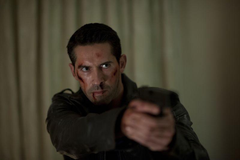 Scott Adkins in Eliminators: Ein Mann mit dunklen Haaren und blutigem Gesicht hält grimmig blickend eine Pistole mit beiden Händen.
