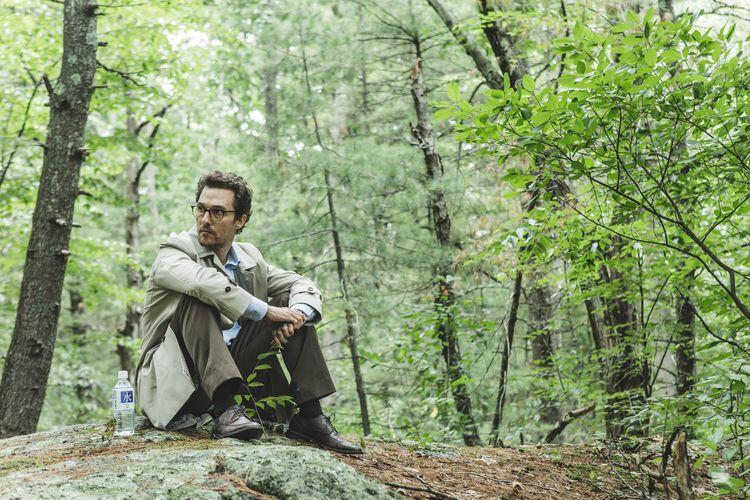 Ein Mann sitzt im Wald.