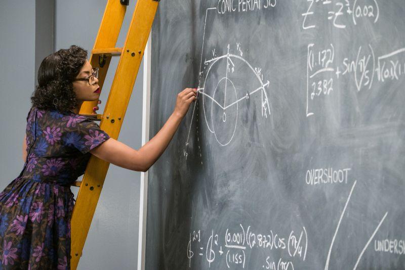 Szene aus Hidden Figures: Eine Frau in einem altmodischen Blümchenkleid lehnt auf einer Leiter und zeichnet mathematische Graphen auf eine Tafel.